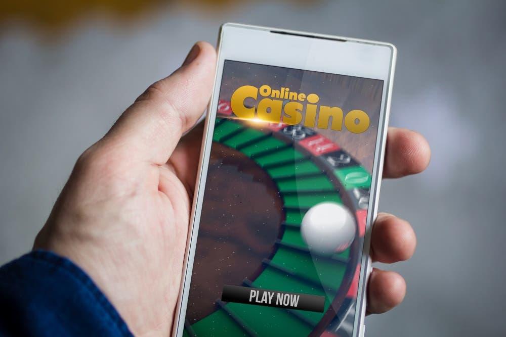 Mensch hält Smartphone mit Roulette-Spiel in der Hand